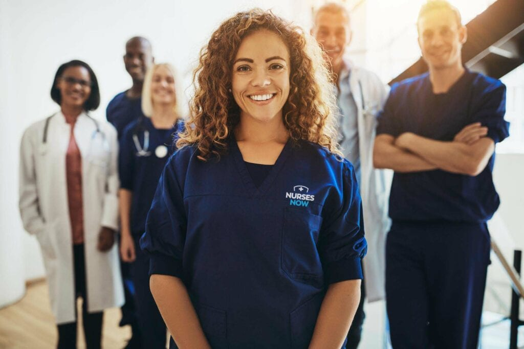 Smiling female doctor standing with medical colleagues in a hospital
